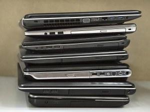 stack of old laptops awaiting repair